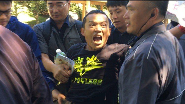 一名到現場陳情的男子,因疑似情緒失控一度遭現場維安人員拉離會場。記者郭頤/攝影