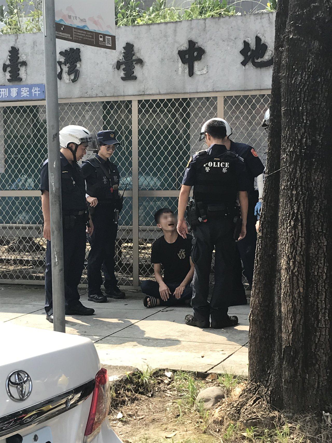 許男(坐者)送友人到地院報到,自己卻涉嫌吸毒遭警攔查逮捕。記者林佩均/攝影