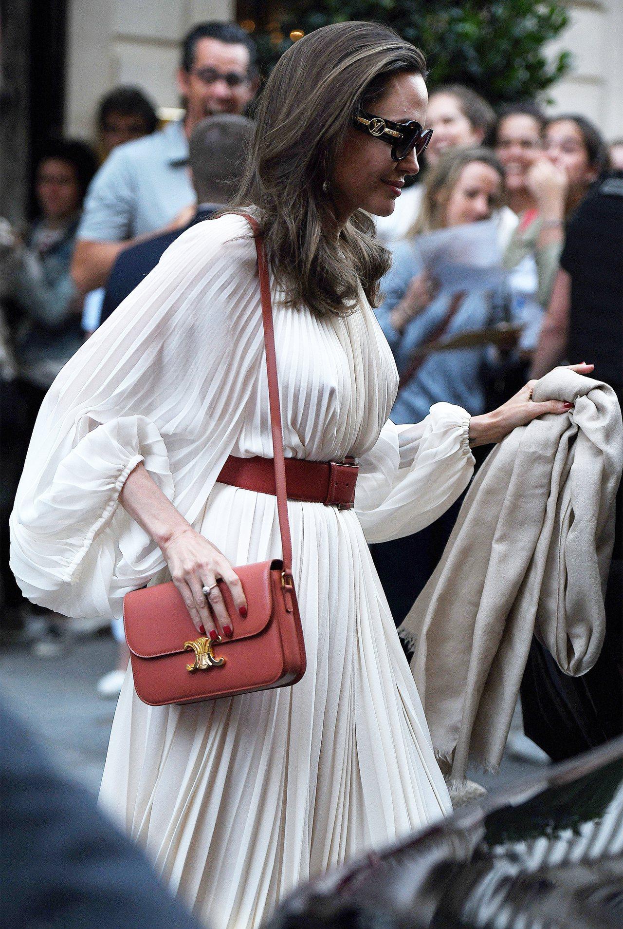 安潔莉娜裘莉身穿THE ROW縐褶長袍,配襯CELINE Triomphe手袋和...