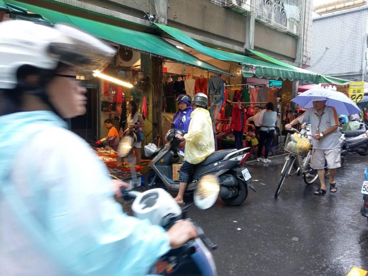 許多民眾擔心颱風過後菜價更高,今天上午紛紛冒雨到傳統市場買菜。記者謝梅芬/攝影