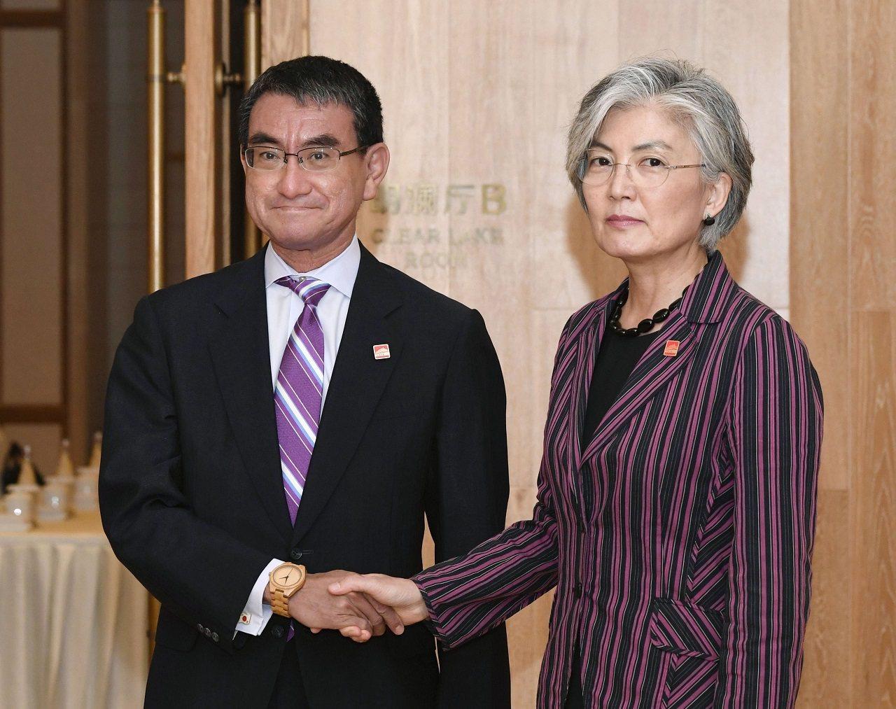 日本外務大臣河野太郎與南韓外長康京和長21日在中國北京會晤前握手供記者拍照。河野...