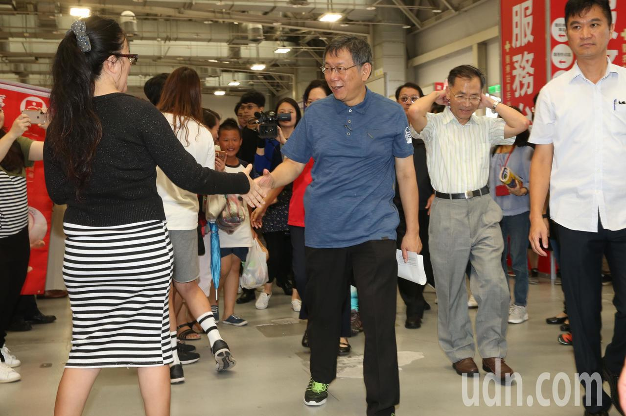 台北市長柯文哲(中)上午參加「青銀共事亮起來」就業博覽會,與參展廠家及求職民眾熱...