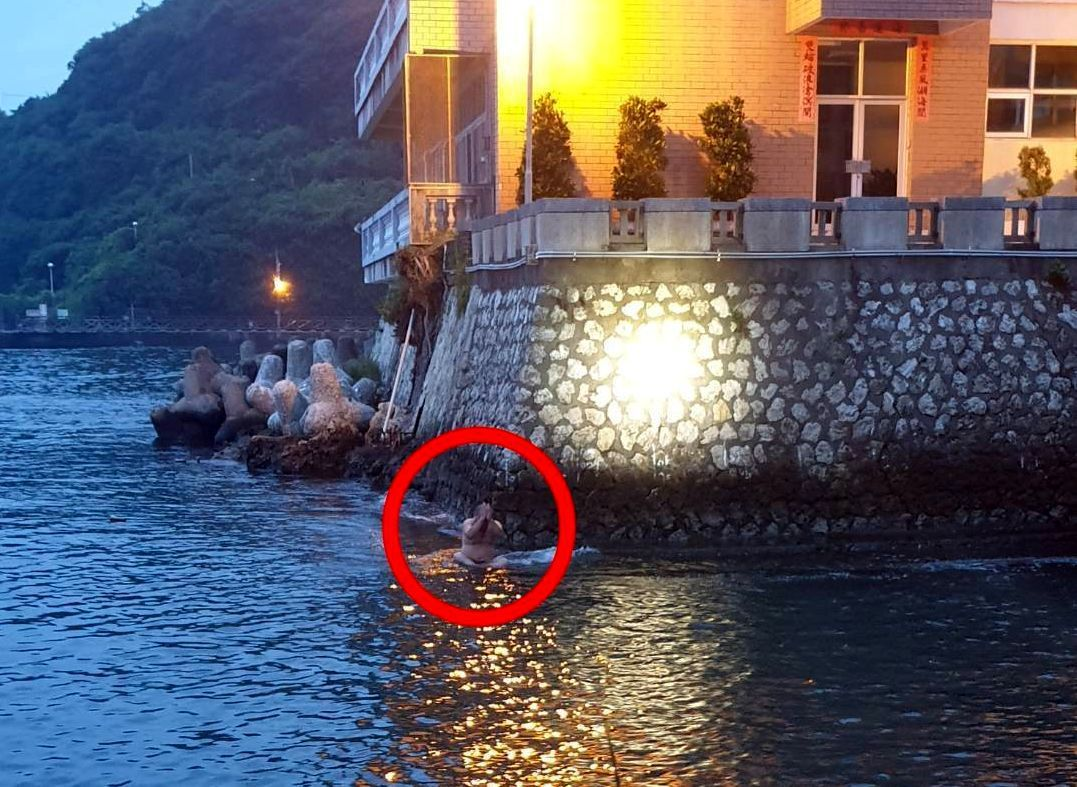 蔡姓男子攀附在水上礁岩,不斷喊叫。記者林保光/翻攝