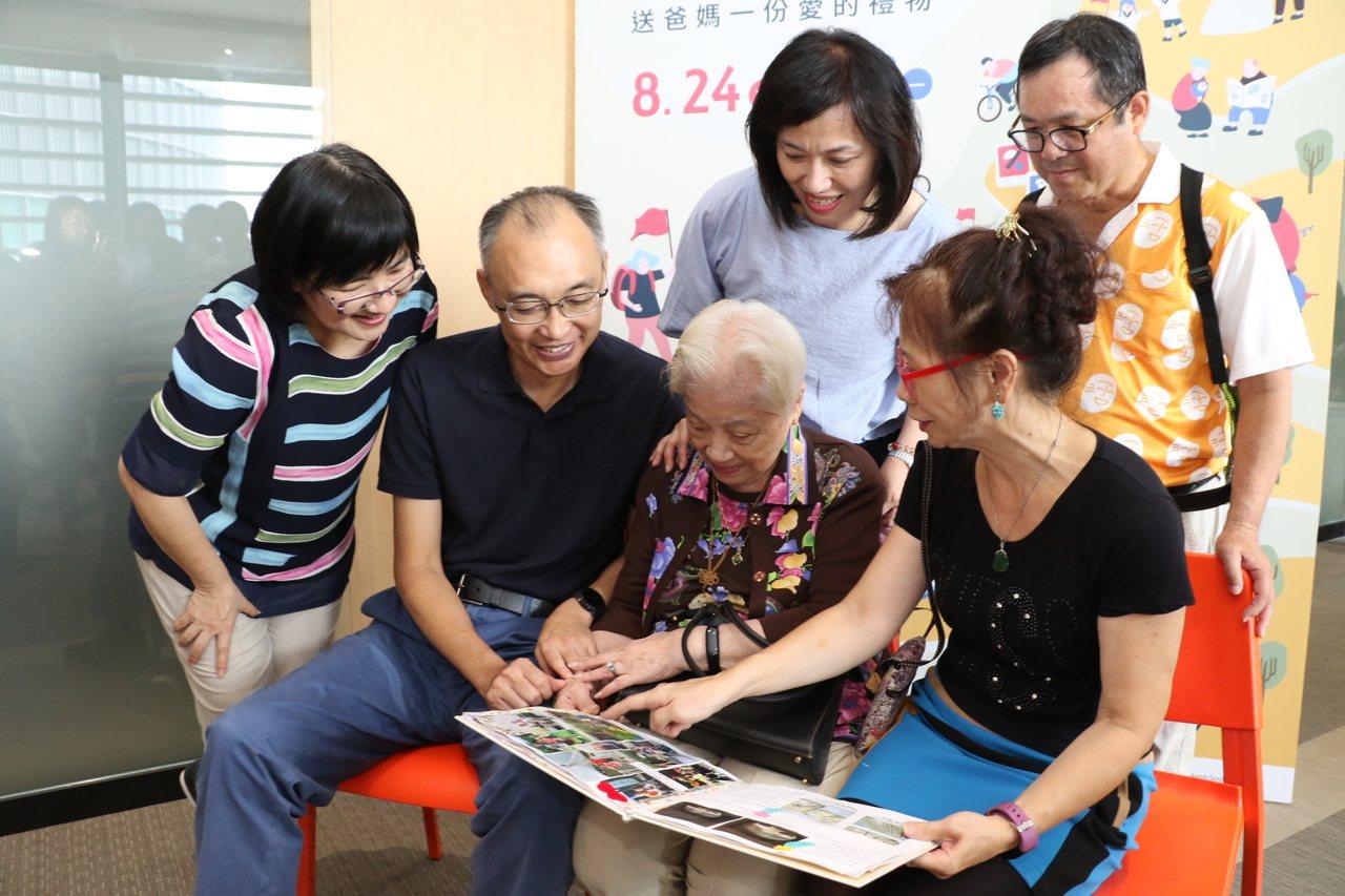 95歲的黃顧月娥(前右二)觀看媳婦葉翠媚(前右一)為她做的生命繪本,非常開心。記...