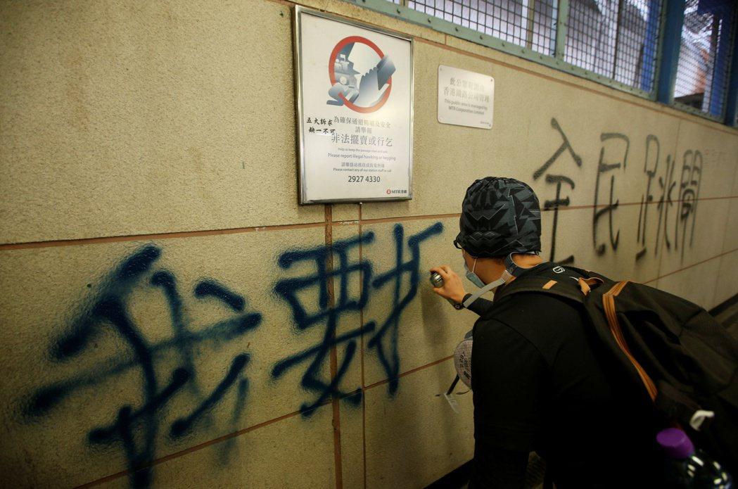 反送中示威者24日在觀塘一帶抗議,並在包括地鐵站等多處塗鴨。(路透)
