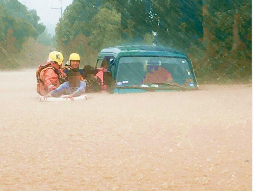 白鹿颱風昨狂掃東部,一名車主受困洪流,由消防人員協助一家四人脫困。 圖/台東縣消...