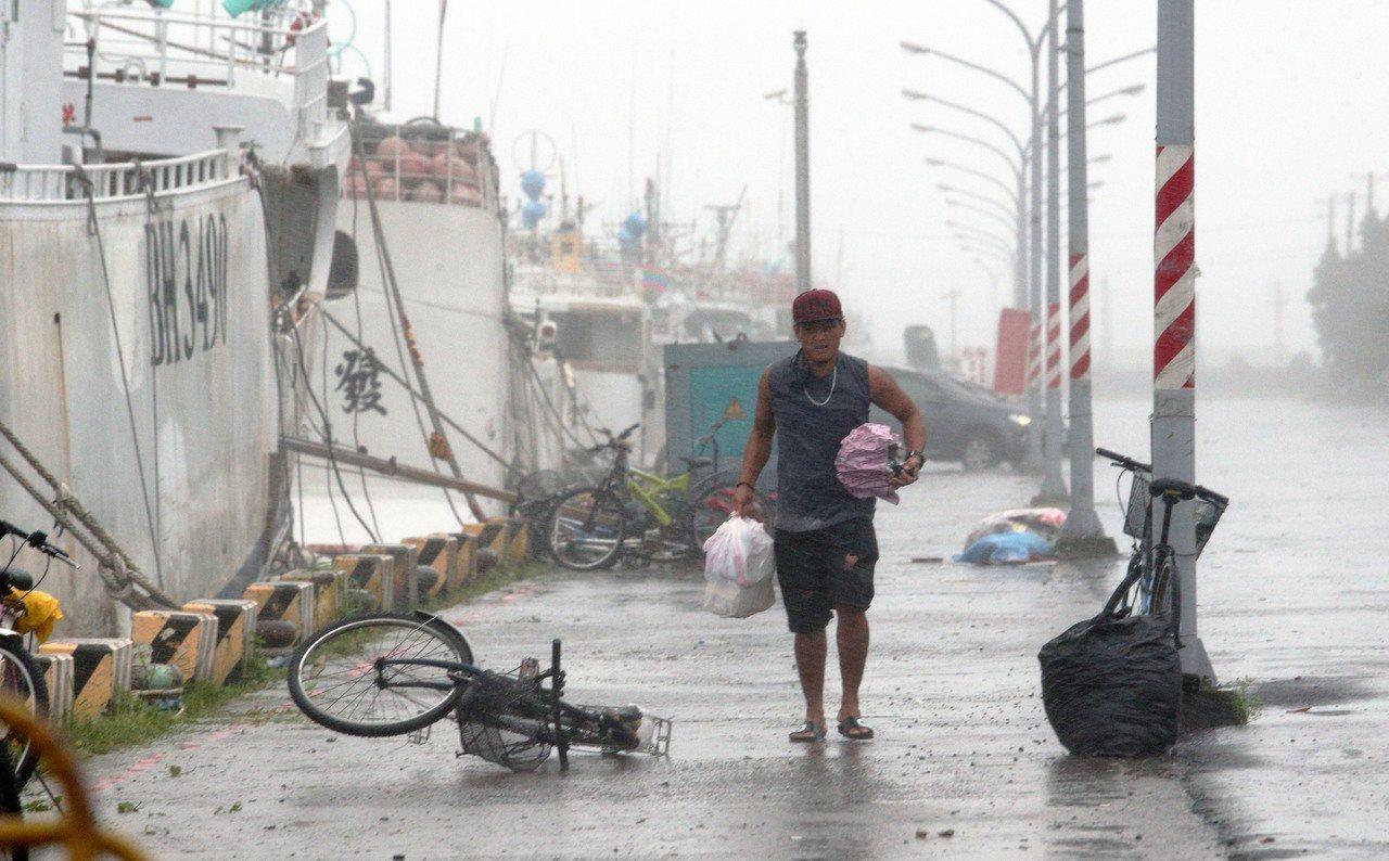 白鹿襲台,屏東東港碼頭許多漁船進港避風,船員冒著風雨採買食物。記者劉學聖/攝影