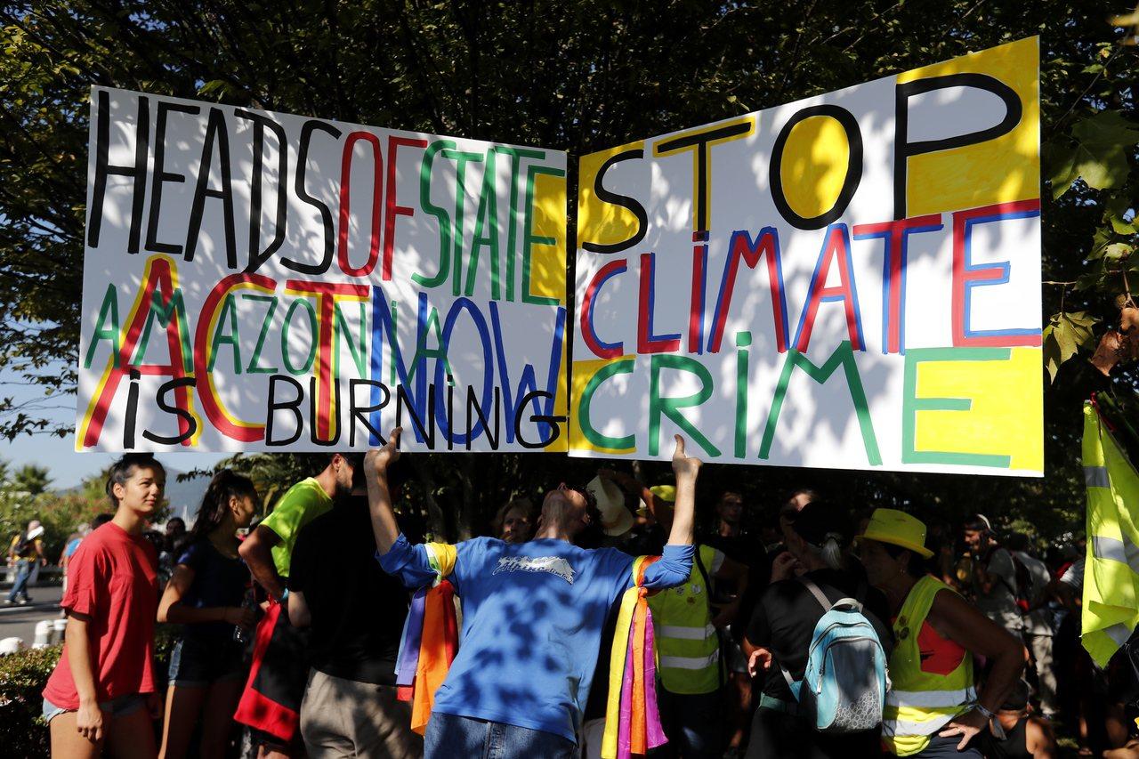 抗議者24日法國比亞里茲G7峰會會場外舉著「國家領導人行動,亞馬遜正在燃燒」和「...