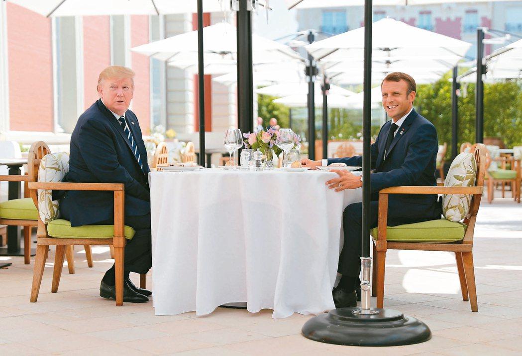 美國總統川普(左)與 G7峰會東道主法國總統馬克宏(右)24日共進午餐,川普表示...