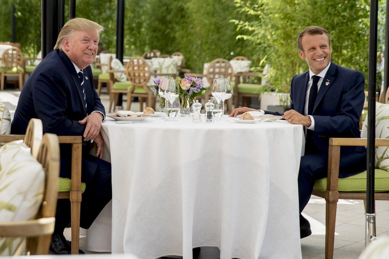 美國總統川普(左)與今年G7峰會東道主法國總統馬克宏(右)24日共進午餐,川普表...