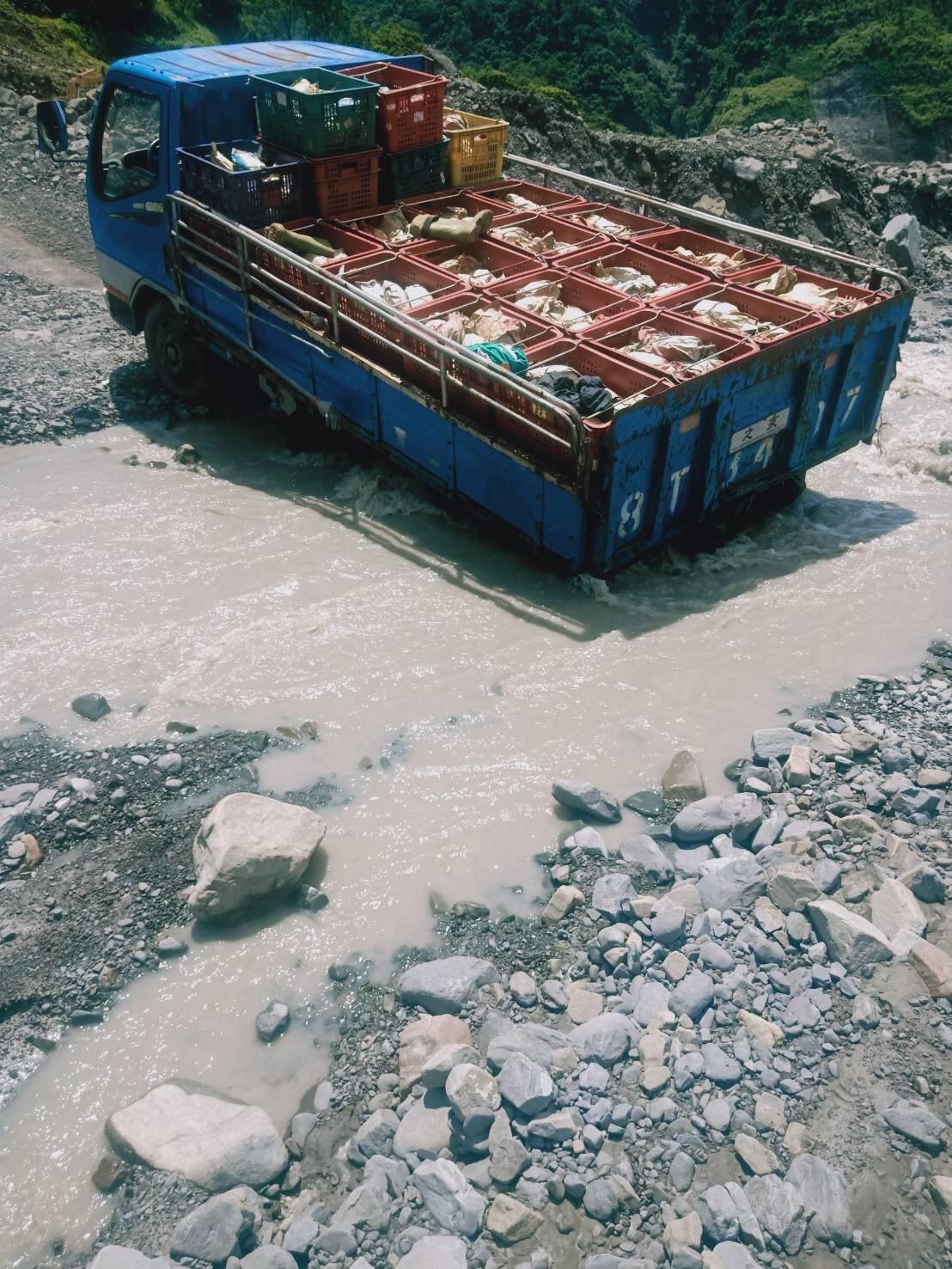 載著一箱箱金煌芒果的貨車有時必須強行穿過溪床。圖/高雄市農業局提供