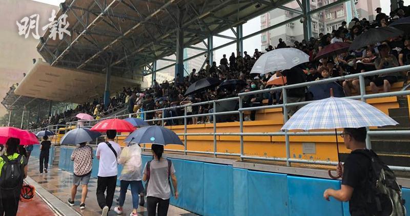 在葵涌運動場,參與遊行的人潮不絕,市民為避雨坐滿運動場看台。取自香港明報