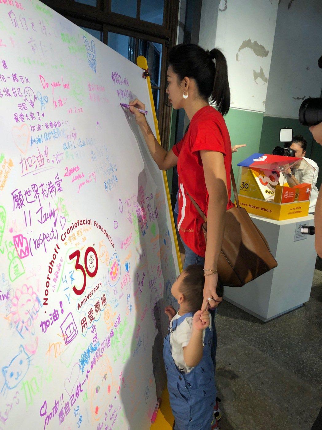 林可彤出席公益活動在背板上簽名。圖/星浪娛樂提供