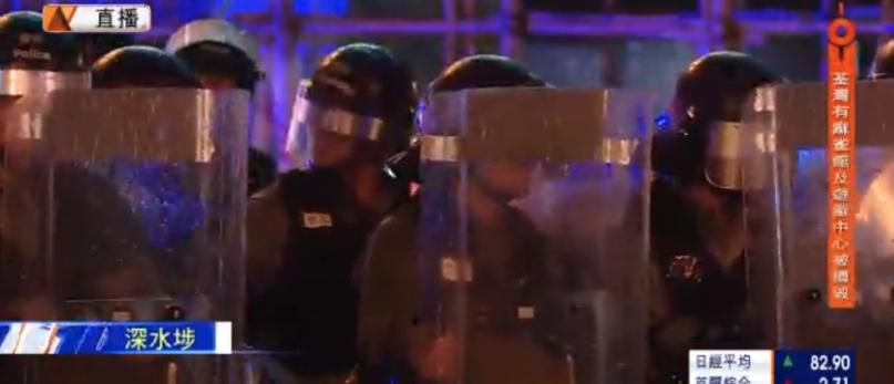 防暴警察在西九龍中心外組成防線,與示威者相隔一個街口對峙。(星島網)