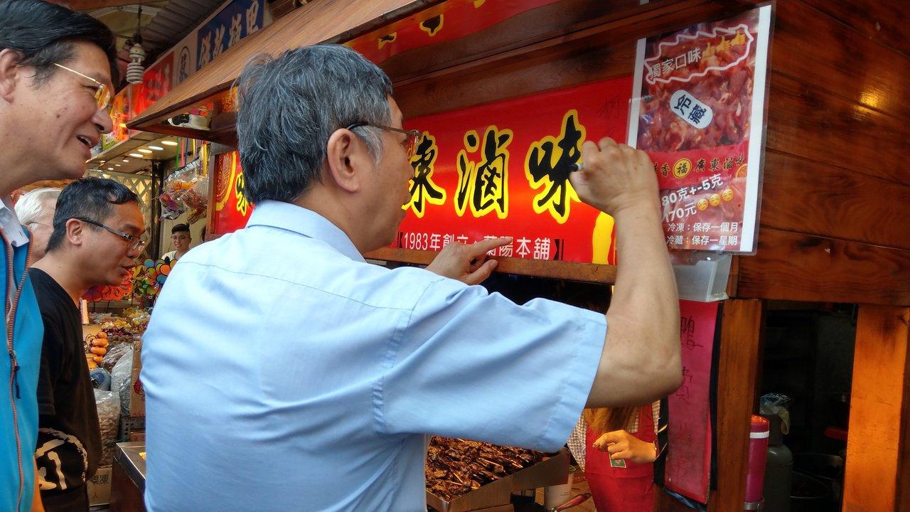 台北市長柯文哲到宜蘭受到熱烈歡迎,在攤商的看板上簽名。 記者戴永華/攝影