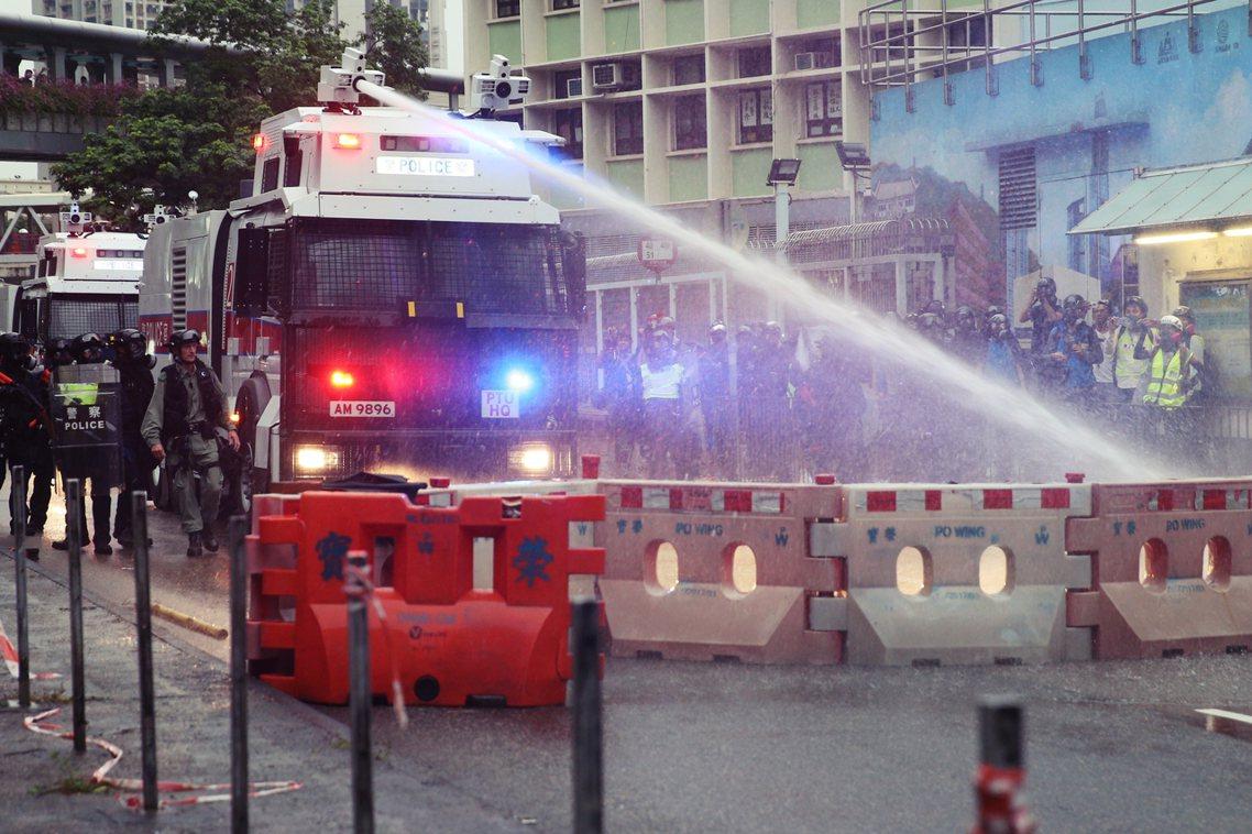現場煙霧彌漫之中,警察也首度出動了水砲車,朝向路障水馬噴水示警。 圖/歐新社