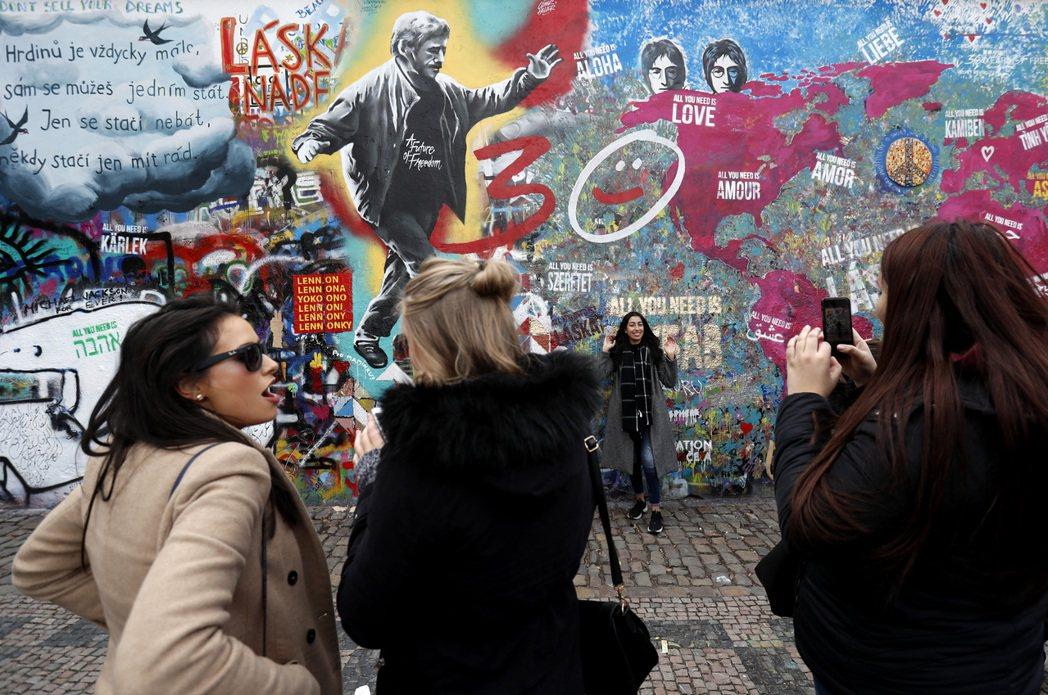 布拉格著名的「藍儂牆」被觀光客寫上淫詞穢語,令當地人覺得難以忍受。圖為觀光客在藍...