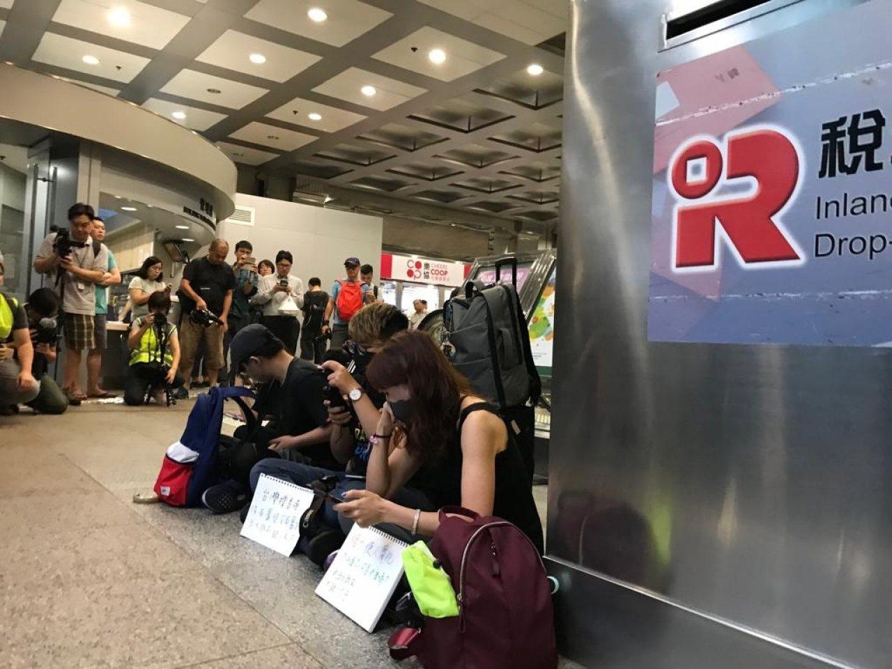 十多人響應號召稅務大樓靜坐,有台灣旅客參與。取自香港電台
