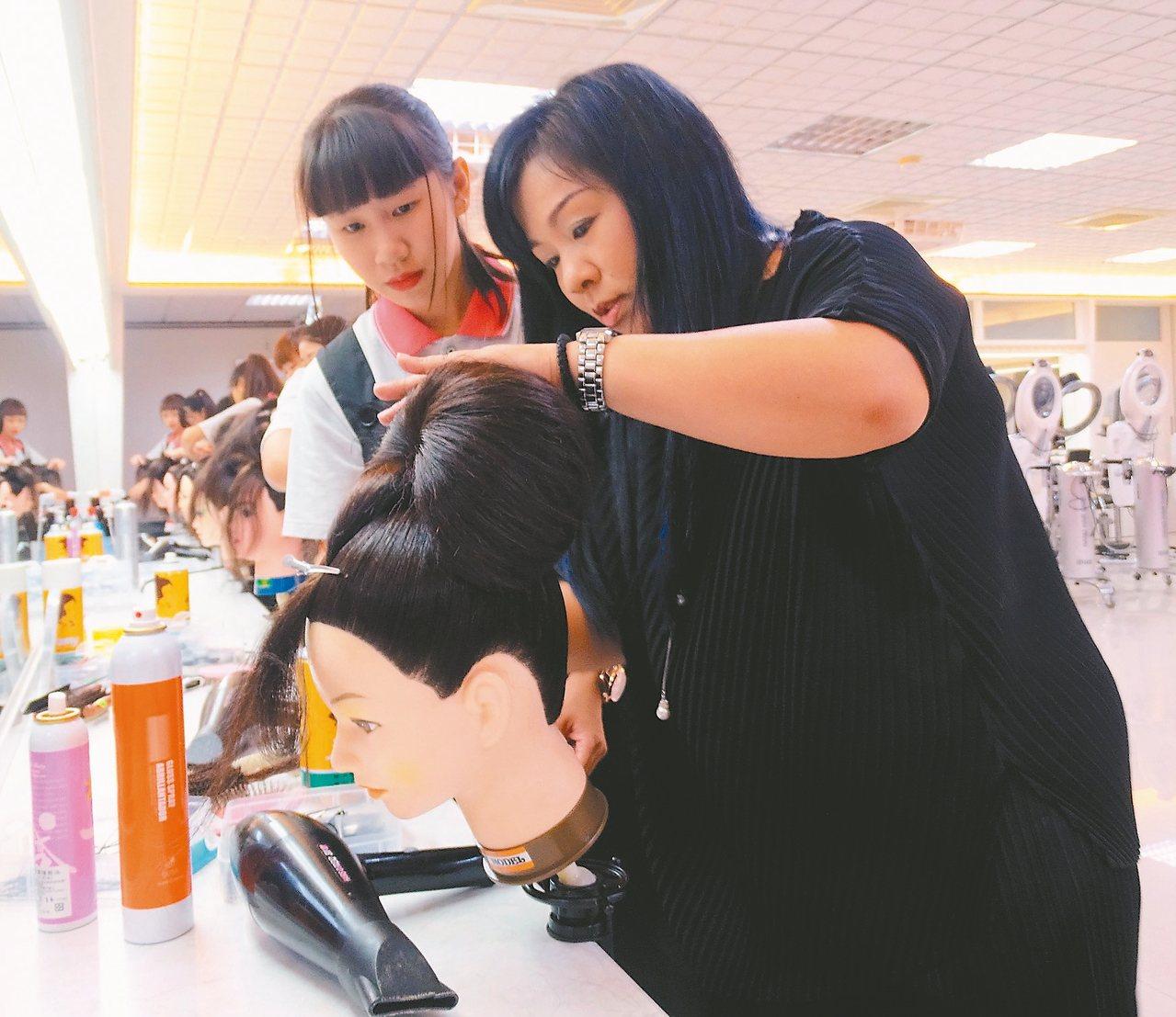 達德商工美容科老師藍雅惠(右)示範梳出完美的包頭。 記者凌筠婷/攝影