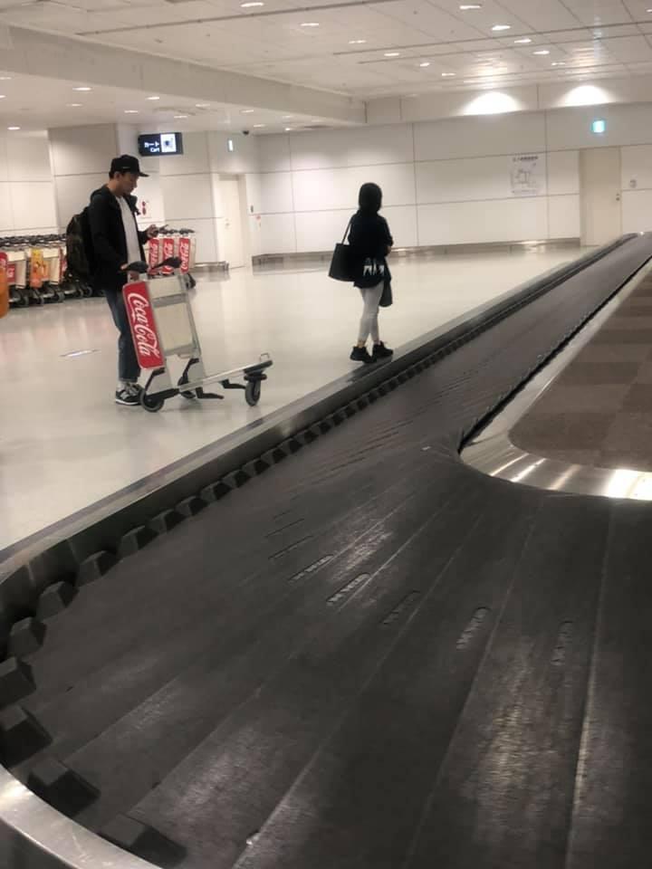 張震一個人在行李轉盤前等行李,老婆則在一旁的椅子上等待。圖/快樂雲提供