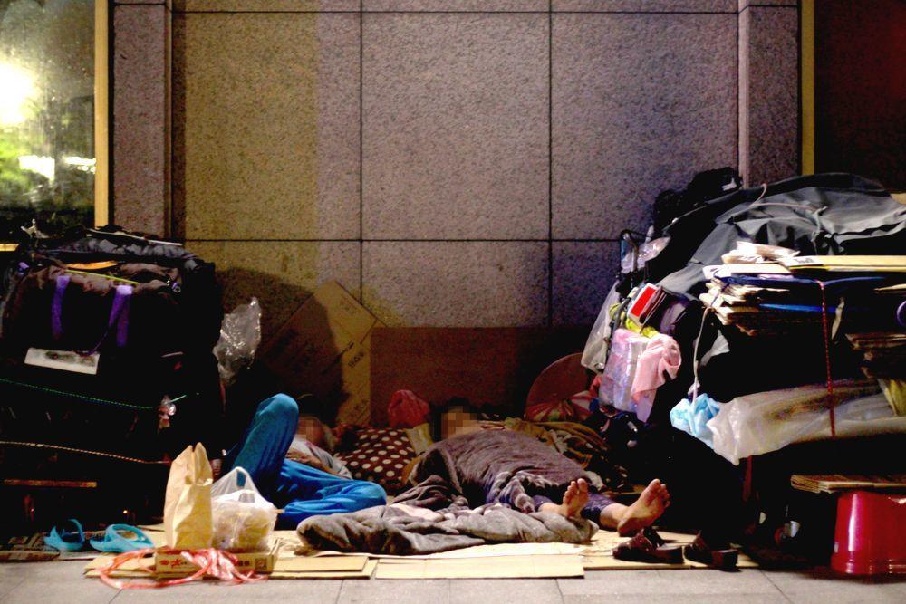 台北車站外的街友睡在雜物之間,紙箱、報紙對他們而言是寶。記者李隆揆/攝影