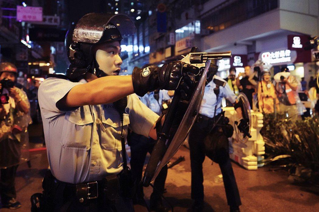 圖為8月25日香港反送中的「荃葵青大遊行」,警察在被示威者追擊之下拔出配槍、其中...