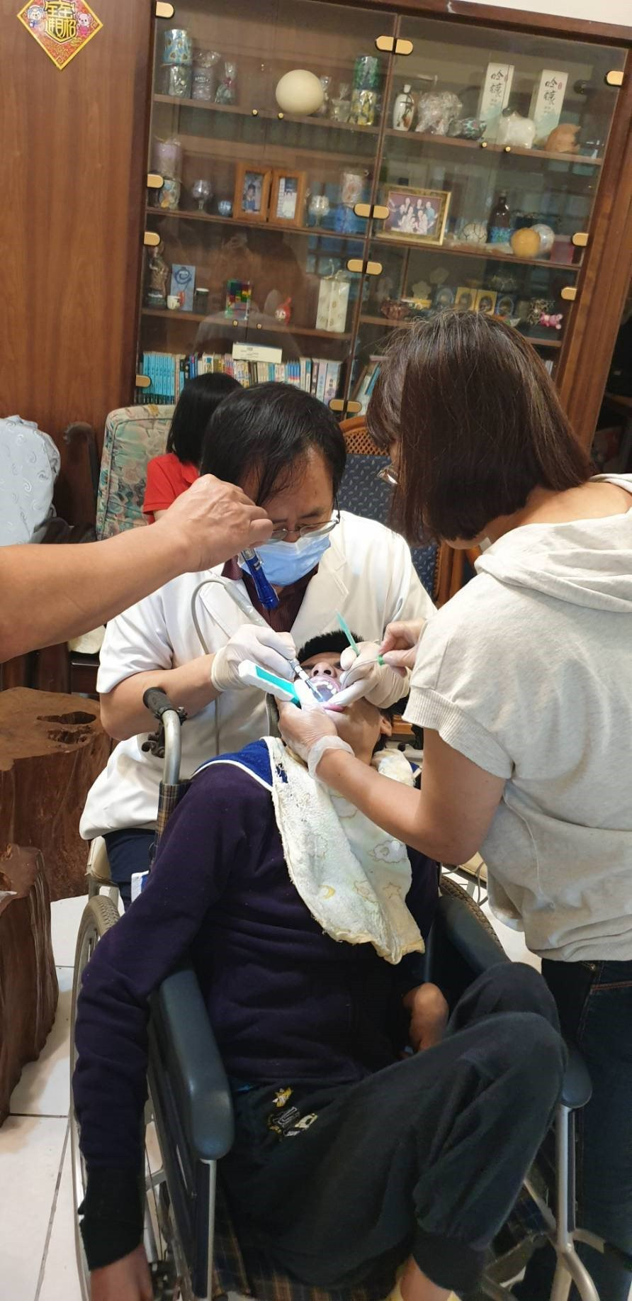 花蓮市林肯牙醫診所院長林易超與團隊投入到宅服務,為坐輪椅的身心障礙者服務。圖/林...