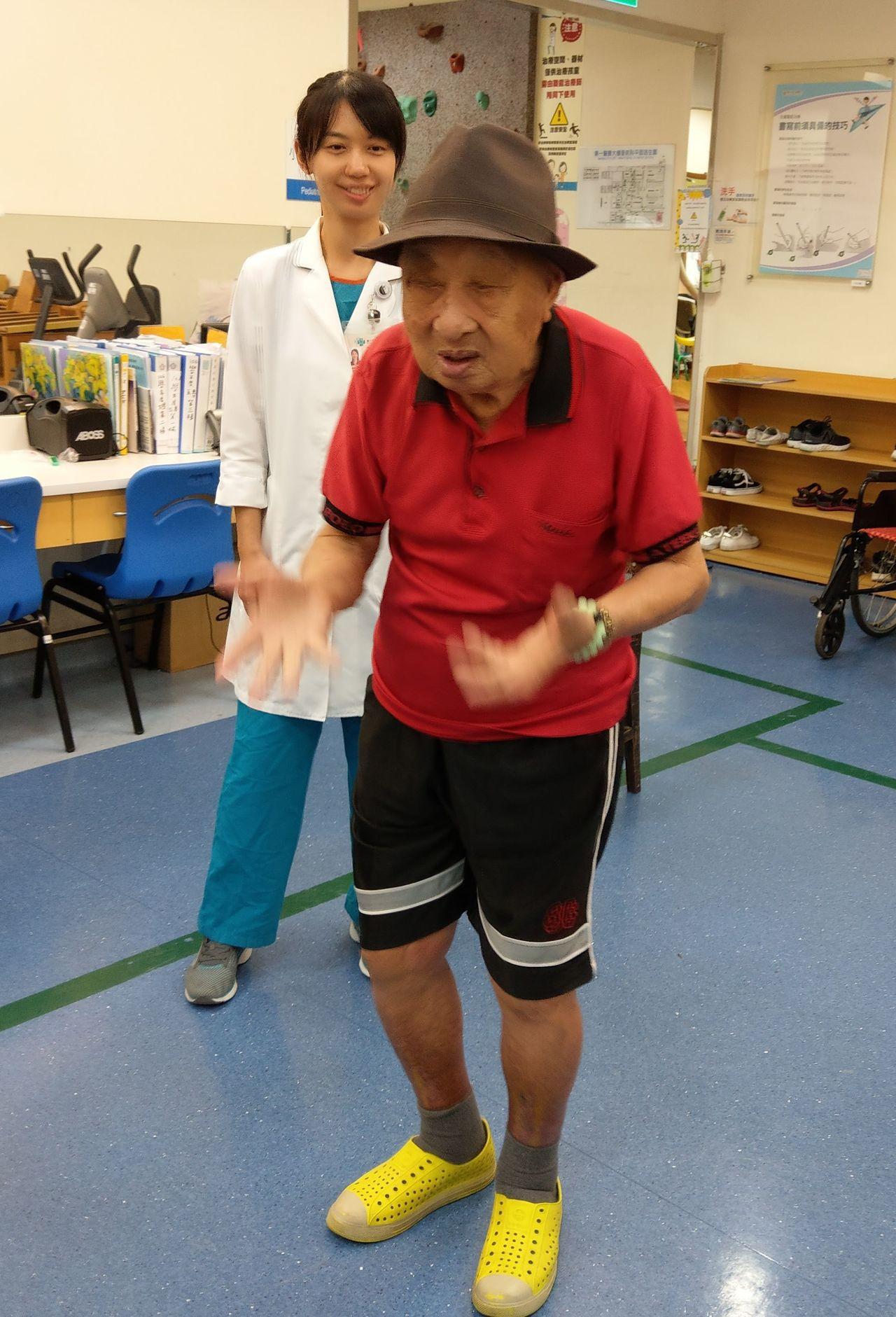 周懷春將軍(右)今天在台中榮總復健科歡度105歲生日,開心示範平時自創的手舞足蹈...