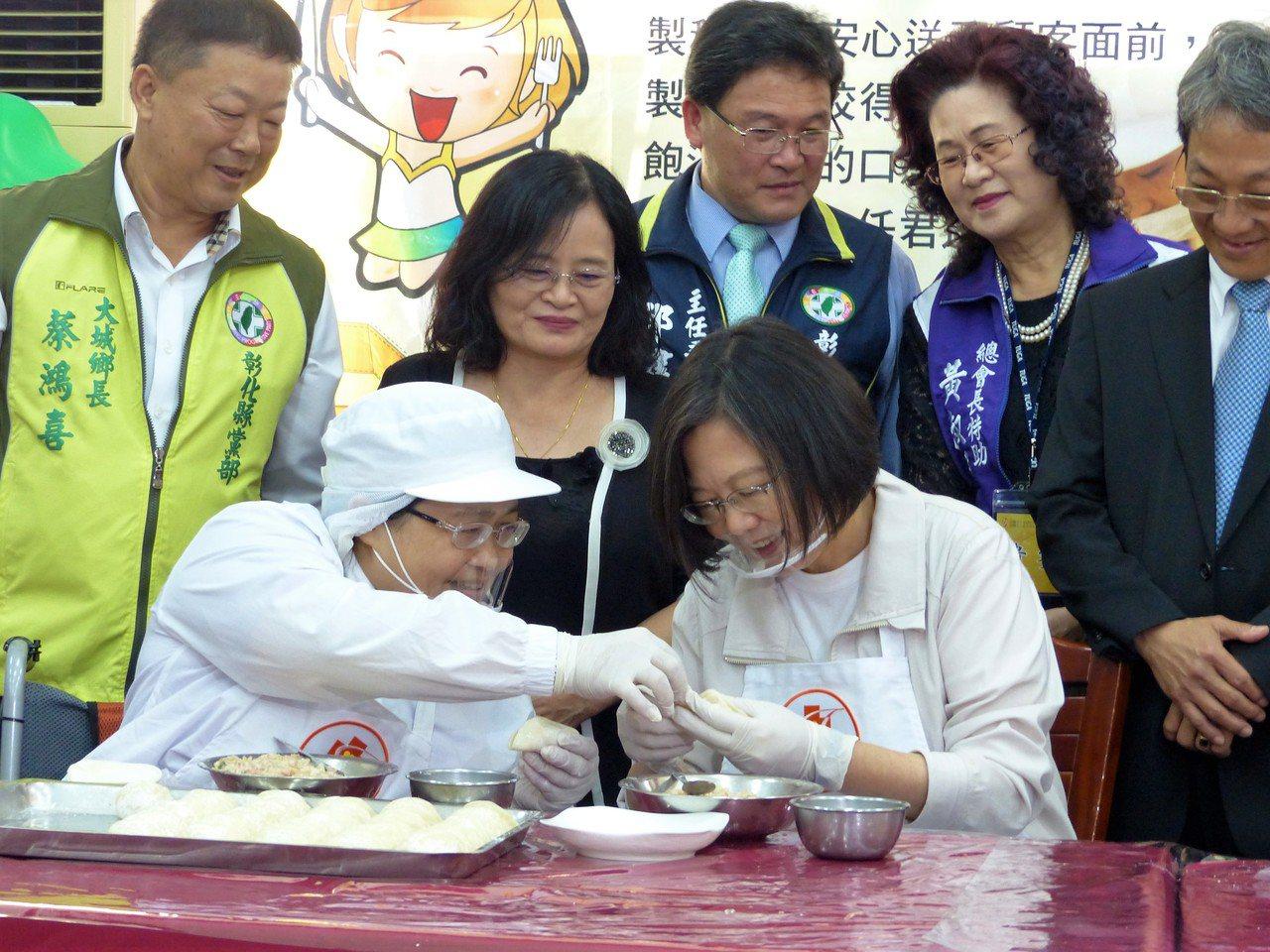總統蔡英文向喜樂水餃坊的工作夥伴學習如何包出漂亮的水餃。記者凌筠婷/攝影