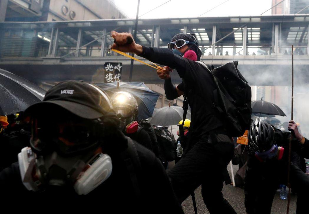 一名香港示威者以彈弓反制警方攻勢。 圖/路透社