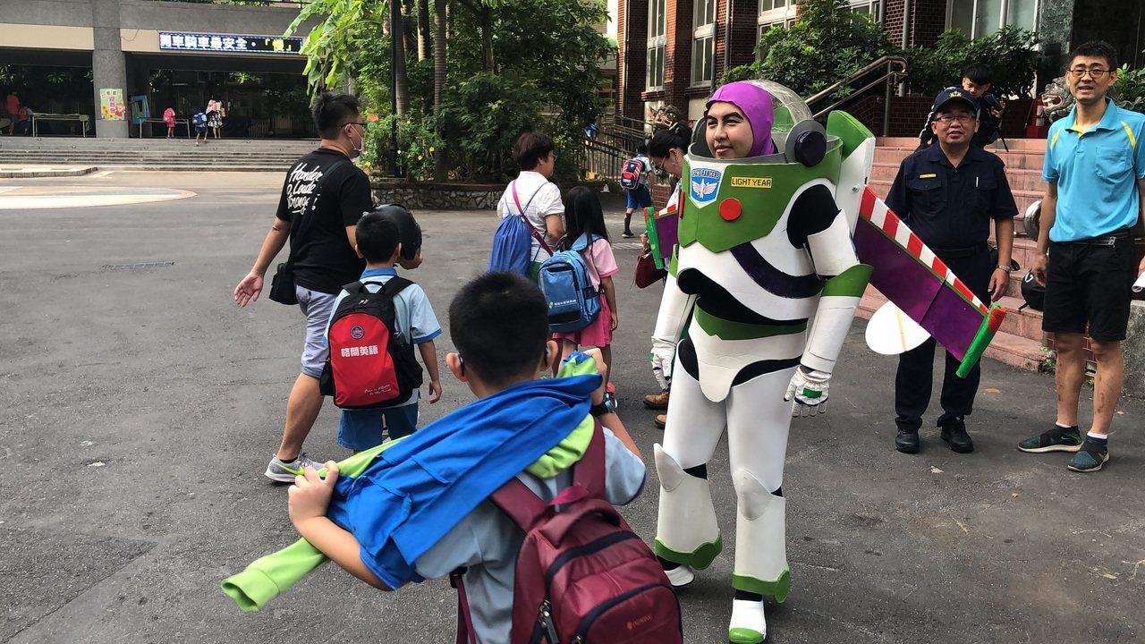 第一分局巡官吳秉陽昨裝扮成巴斯光年太空騎警,到仁愛、信義國小護童。圖/警方提供