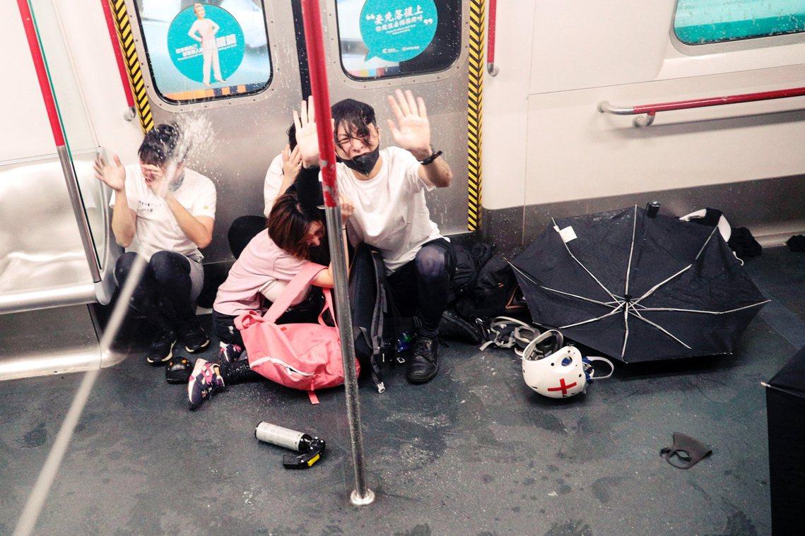 被無差別攻擊的市民瑟縮在車廂地上抱成一團,有戴口罩、穿白衣的市民跪在地上請求警察...