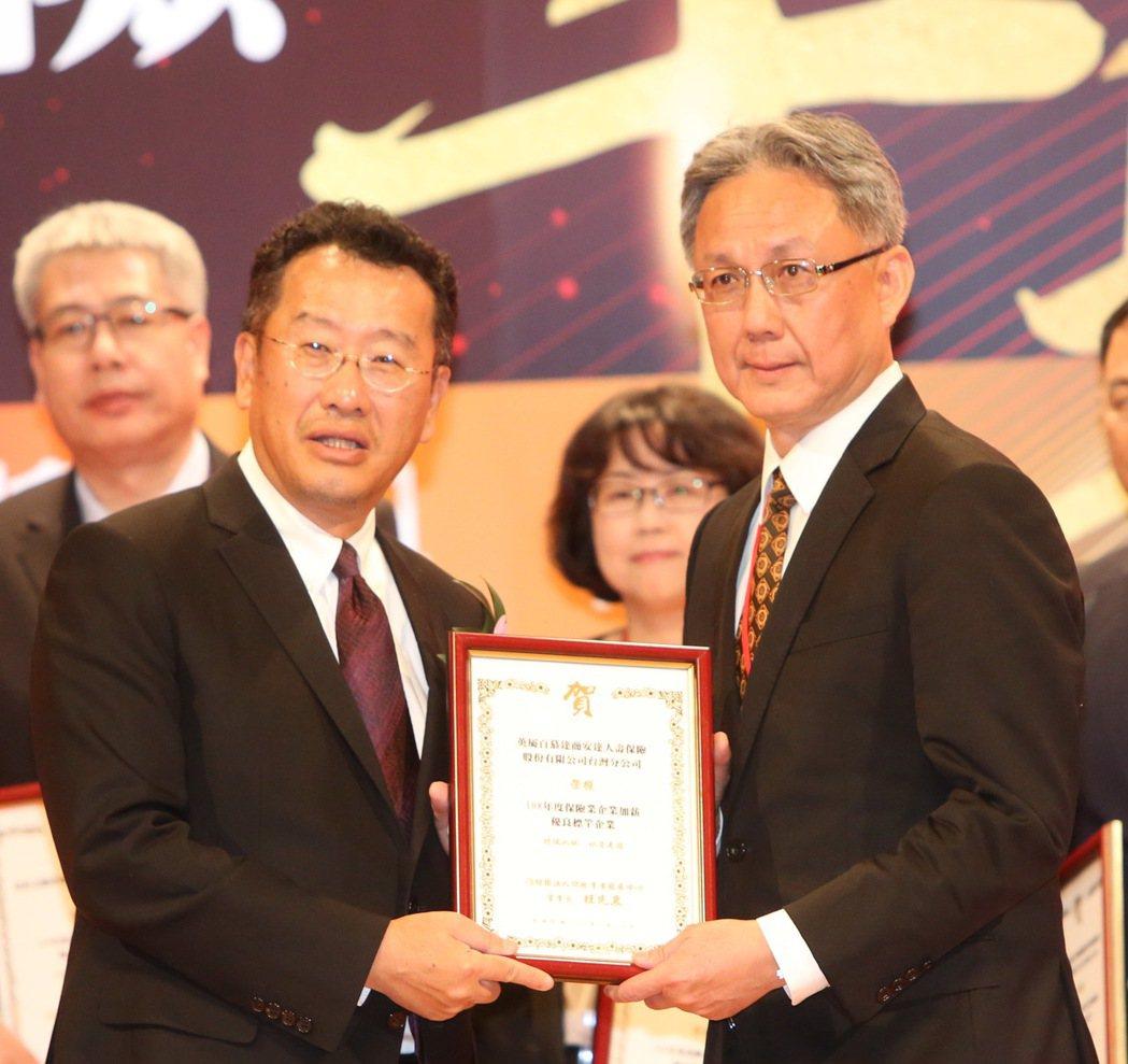 安達人壽首席營運總監林意展(右)代表接受金管會主委顧立雄表揚。 毛洪霖/攝影