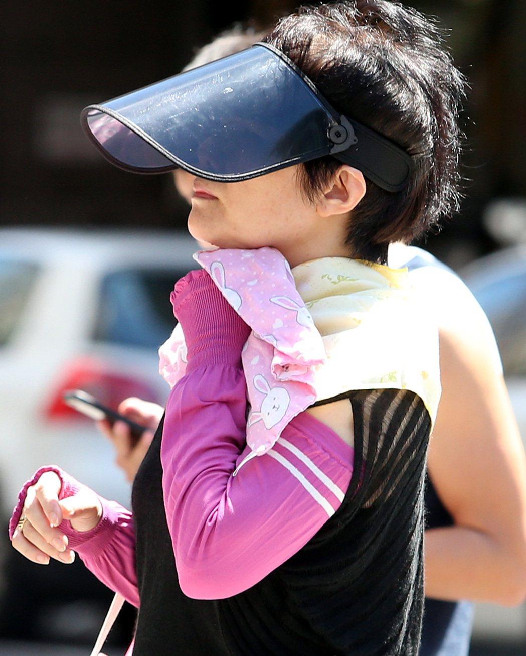 氣象局針對大台北地區及桃園市發布黃色燈號的高溫資訊,外出婦女戴遮陽帽、防曬袖套及...
