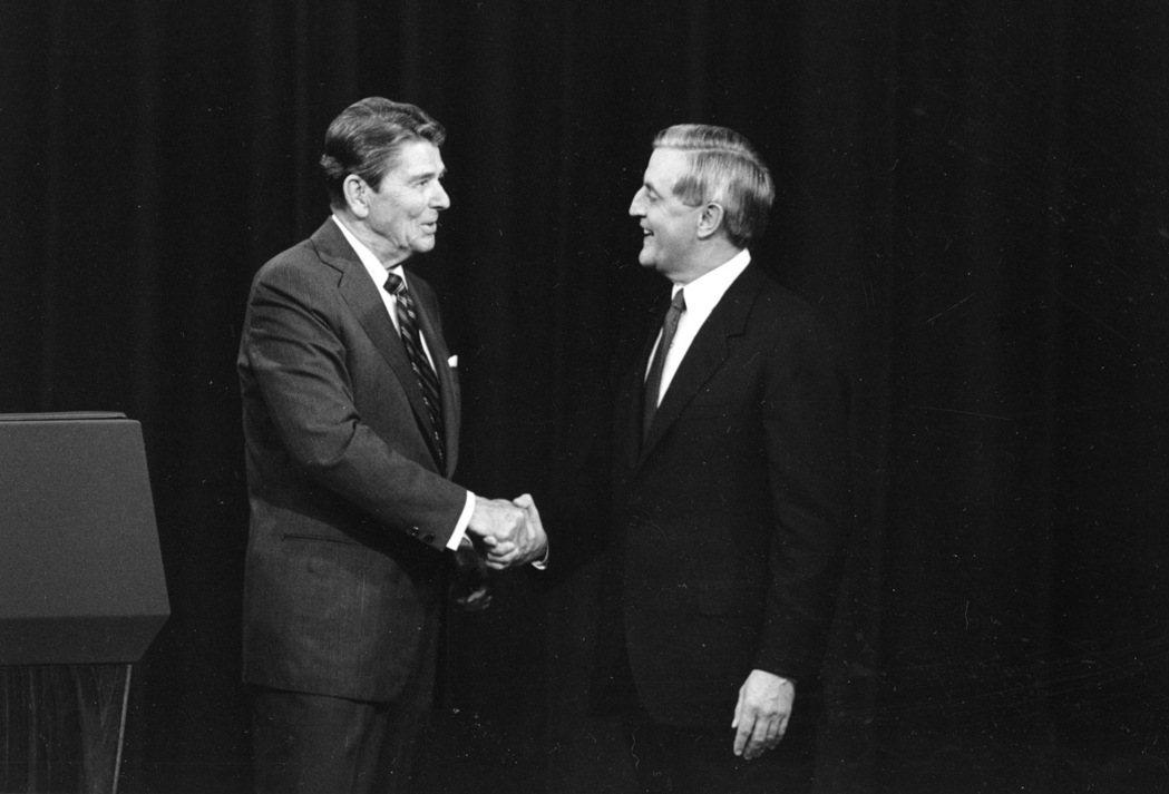 1984年總統大選電視辯論會,時任美國總統的雷根(左)跟民主黨挑戰者孟岱爾握手寒...