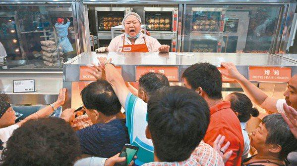 湧入好市多上海店的顧客擠成一團搶購烤雞,售貨員大叫不要推擠。 (法新社)