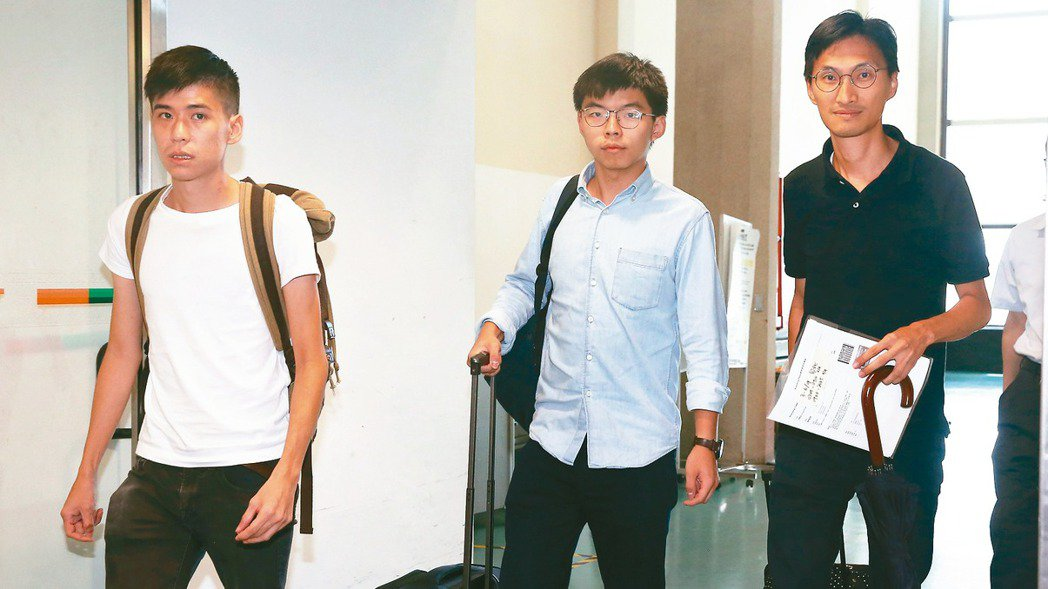 香港眾志秘書長黃之鋒(中)、學聯前副秘書長岑敖暉(左)、立法會議員朱凱迪(右)等...