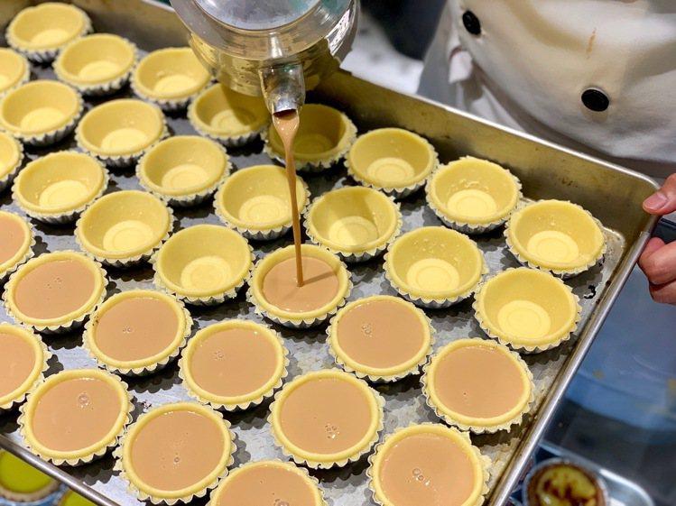 在曲奇塔皮倒入奶茶蛋液,「港式奶茶蛋撻」每顆售價40元。記者張芳瑜/攝影