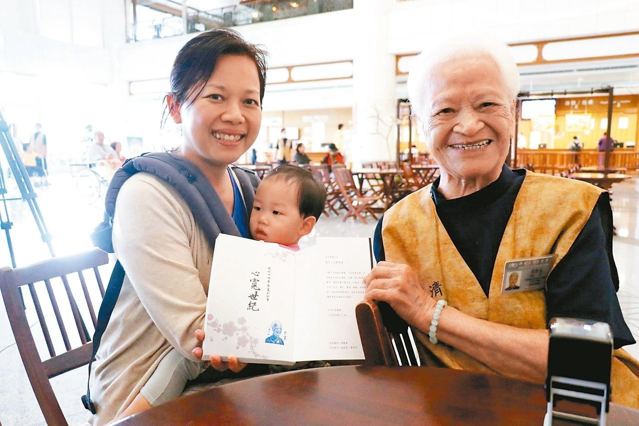 周小姐(左)因媽媽喜歡蔡寬阿嬤(右),特地抱著女兒到簽書會,請阿嬤親自蓋章並合影...
