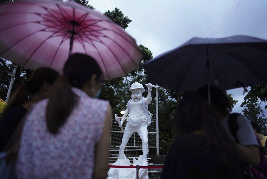 港人籌款打造的「香港民主女神像」,頭戴頭盔、眼罩及防毒面具,手上拿著雨傘及「光復香港、時代革命」旗幟。攝於9月2日。 圖/美聯社