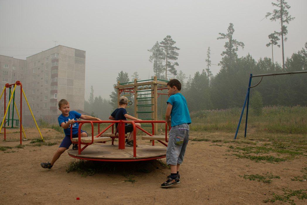 伊爾庫次克森林大火濃煙讓天空灰濛濛的,孩童照玩不誤。 (路透)