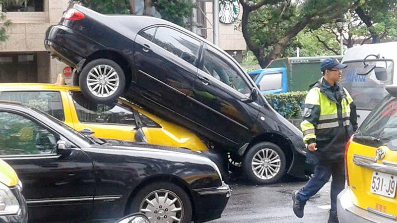 陳姓男子駕駛黑色轎車行經承德路時,不慎撞上前方計程車,竟又倒車「騎上」後方計程車。圖/翻攝自臉書社團加藤軍台灣粉絲團2.0