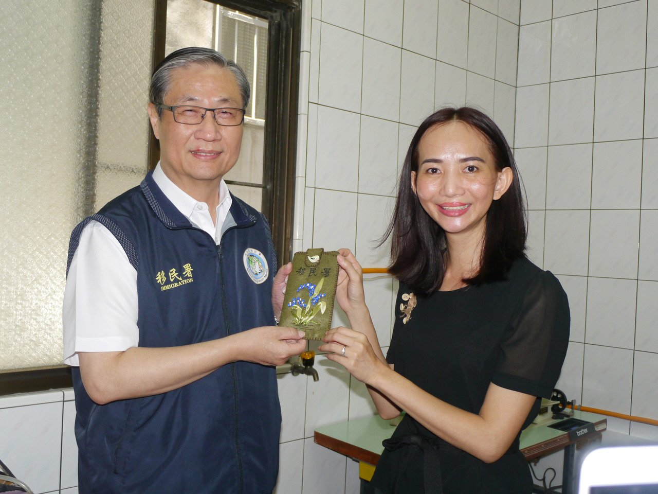 移民署副署長鐘景琨(左)南下訪視,越南籍新住民陳黃燕(右)贈送手作手機袋,感謝移...