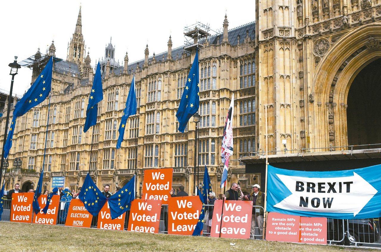 英國府會因為脫歐問題僵持,圖為支持脫歐的民眾在國會外持標語表達立場。 美聯社