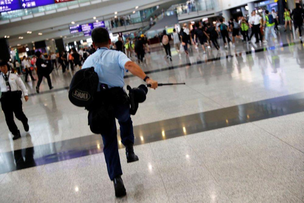 9月1日,一名港警在香港國際機場追捕反送中示威者。 圖/路透社