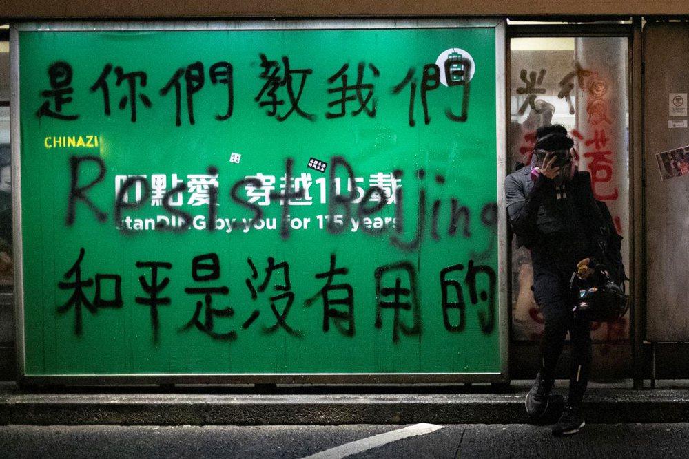 有示威者在香港街頭塗鴉,寫上「是你們教我們,和平是沒有用的」。 圖/路透社