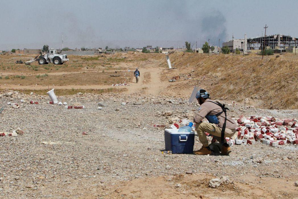掃雷人員正對拜吉附近一處農田進行掃描工作。 (法新社)