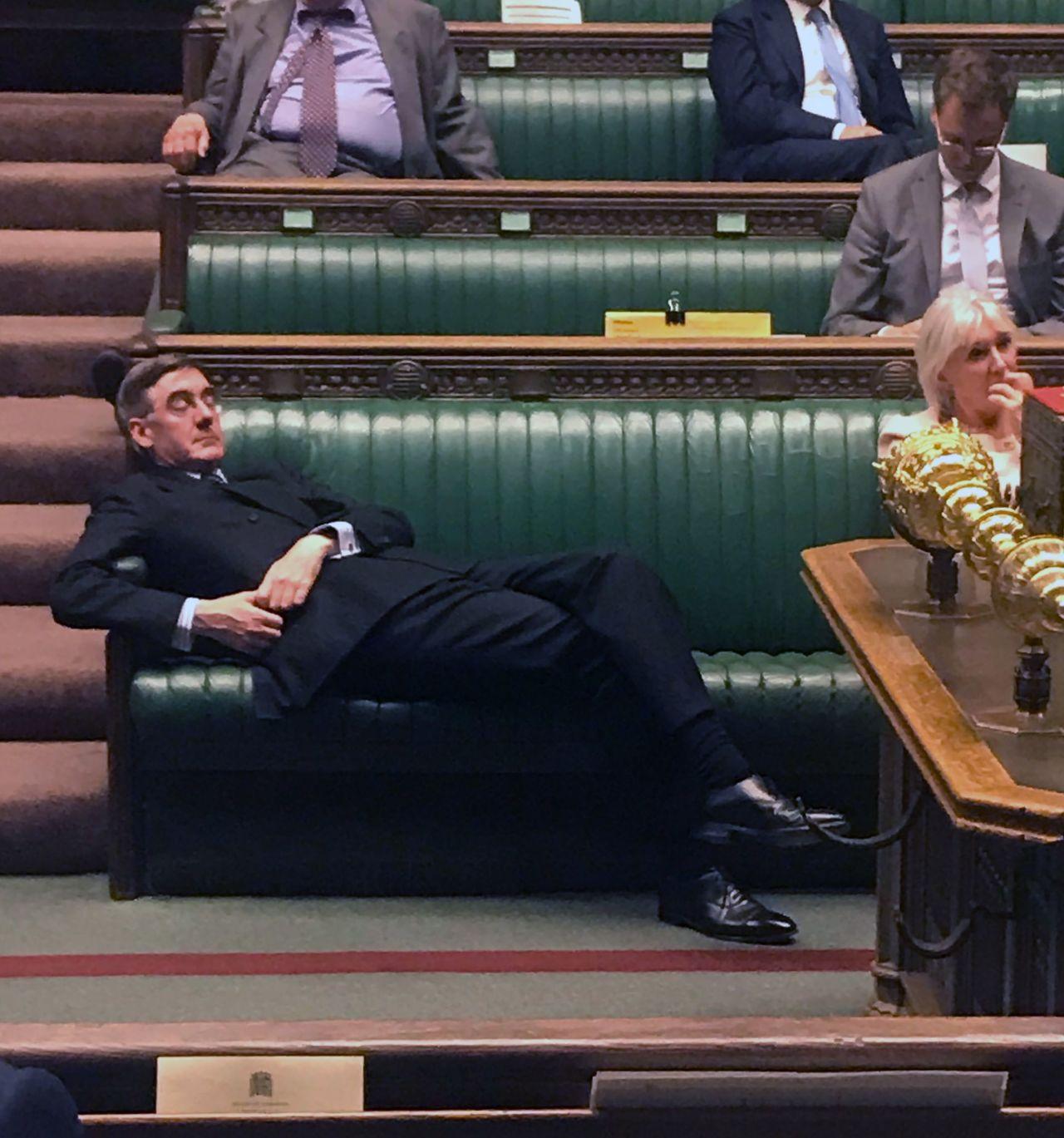 英國保守黨下議院領袖芮斯莫格3日在國會進行辯論時大剌剌攤在座椅上,被視為英國國會...