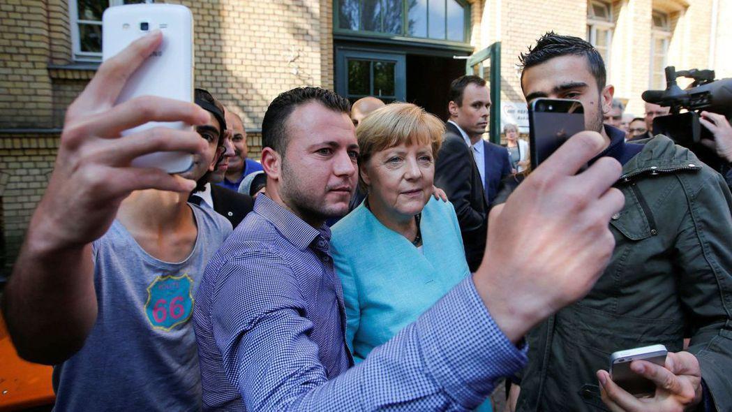 來自敘利亞和伊拉克的移民與德國總理梅克爾用手機自拍合照。梅克爾開門接納難民的政策...