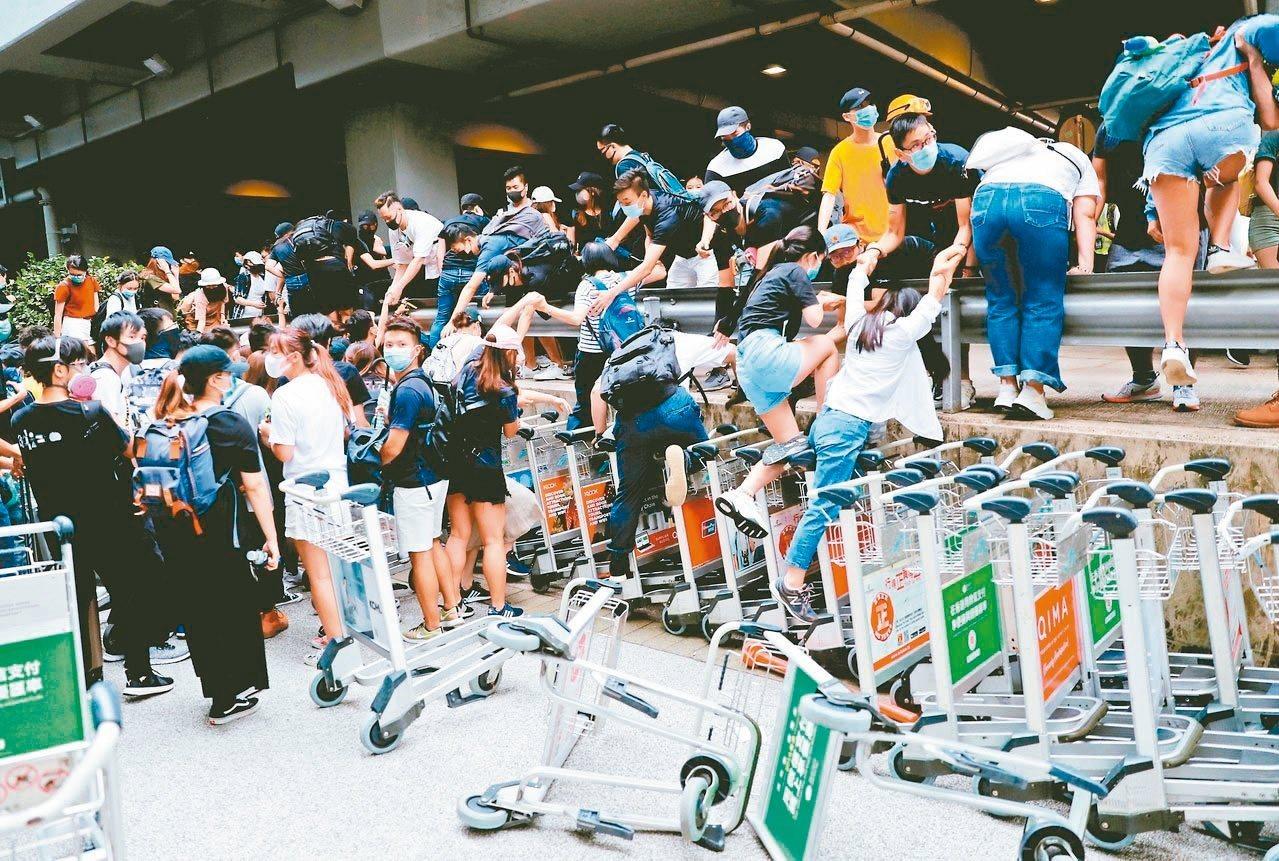 反送中示威者在香港機場航廈外的巴士站,被防暴警察驅散。 (路透)
